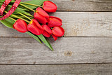 Fresh red tulips bouquet over wooden table background