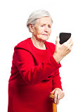 Upset elderly woman using touch screen mobile for taking selfie or making video call