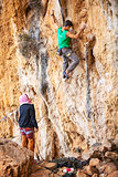 Young man lead climbing on natural cliff, belayer watching him