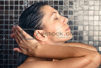 Attractive woman washing her hair in the shower