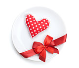 Valentine's Day heart shaped toy over plate with red bow