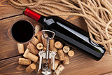 Red wine bottle, glass, corks and corkscrew. View from above