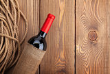 Red wine bottle over rustic wooden table background