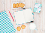 Notepad, cup of milk, heart shaped cookies and gift box