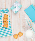 Cup of milk, heart shaped cookies and gift box