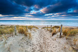 sand path to North sea coast at sunset