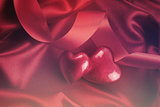 Red hearts on satin background