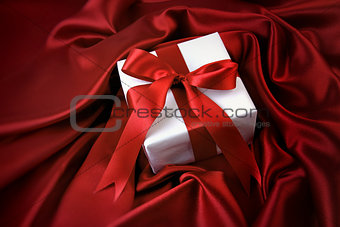 Small valentine gift on red satin