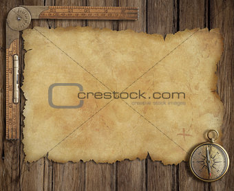 old treasure map on wooden desk with compass and ruler