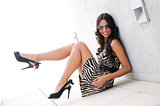 Funny Female model at fashion with high heels sitting on the flo