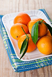 tangerines with leaves in plate