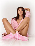 Beautiful woman in pink cosy sleepwear on the bed.