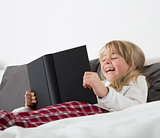 Laughing Young Girl Reading a book