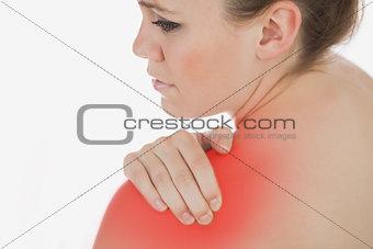 Topless woman massaging her shoulder