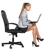 Businesswoman sitting on the edge of office chair, with laptop