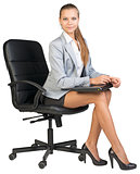 Businesswoman on office chair, holding closed laptop