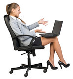 Businesswoman on office chair with laptop, looking and pointing at the blank screen