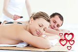 Composite image of young couple having a massage with hot stone