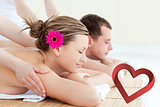 Composite image of relaxed couple having a back massage