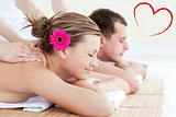 Composite image of relaxed young couple receiving a back massage