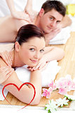 Composite image of merry young couple enjoying a back massage