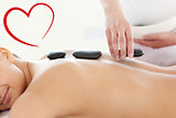 Composite image of portrait of a beautiful woman having a massage with stones