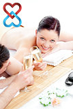 Composite image of young couple lying on a massage table and drinking champagne