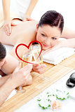 Composite image of young couple enjoying a back massage and drinking champagne