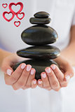 Composite image of beauty therapist holding pile of stones for massage