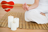 Composite image of woman sitting in lotus pose beside white candles