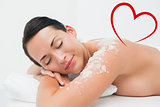 Composite image of peaceful brunette lying with salt scrub on shoulders