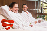 Composite image of smiling women in bathrobes sitting on couch