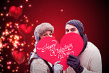 Composite image of attractive young couple in warm clothes holding red heart