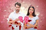 Composite image of upset couple holding two halves of broken heart