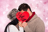 Composite image of young couple kissing behind red heart