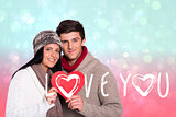 Composite image of young couple smiling holding red heart