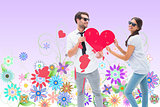 Composite image of hipster couple smiling at camera holding a heart