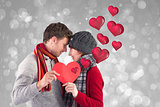 Composite image of couple holding a red heart