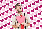 Composite image of geeky hipster crying and holding heart card