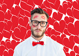 Composite image of geeky hipster with kisses on his face
