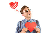 Composite image of geeky hipster holding a heart card