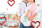 Composite image of close up of a bright pregnant woman holding baby shoes while husband touching her