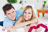 Composite image of smiling beatiful couple sitting on a sofa