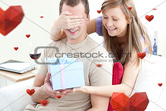 Composite image of smiling woman giving a present to her boyfriend