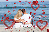 Composite image of affectionate couple sitting on the sand at the beach