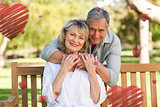 Composite image of elderly man hugging his wife who is on the bench