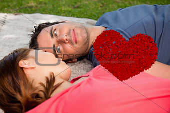 Composite image of man looking into his friends eyes while lying on a quilt