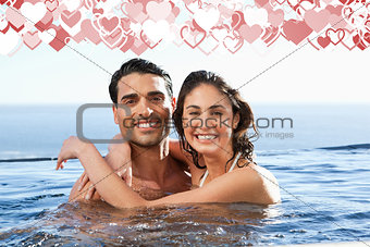 Composite image of smiling couple embracing in the pool
