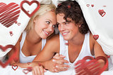 Composite image of portrait of an in love couple under a duvet