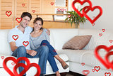 Composite image of couple sitting on a sofa